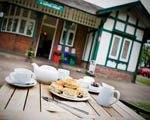 a table laid for a cream tea in front of a red brick building with a green and white gable end