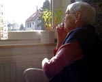 An elderly person sat alone looking out of a window