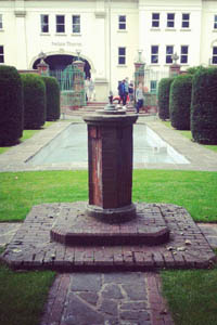 brick plinth in front of italian style garden with pool and formal hedges