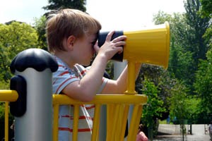 Boy looking through some toy binoculars attached to a yellow climbing frame