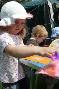 Little girl in a sunhat engaged in a craft activity - sticking feathers to a piece of orange card