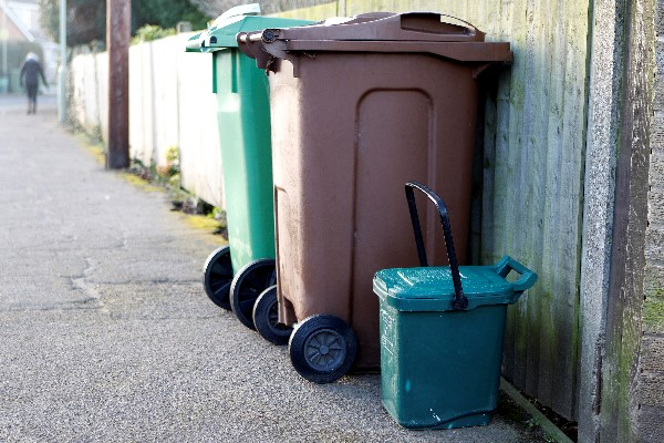 waste and recycling bins put out on a street