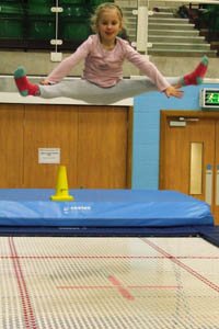 Young girl trampolining. She is high above the trampoline in a straddle jump.