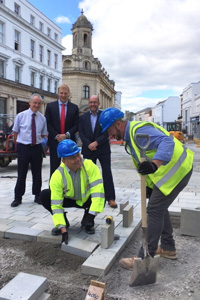 men in high viz jackets and hard hats lay stone slabs on a high street