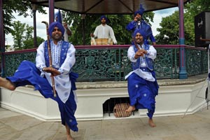 Bangra dancers dressed in blue and white at the Midsummer Fiesta
