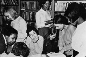 Young white and Caribbean women smiling and looking at books in a library. Black and white photo from around 1960.