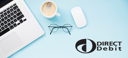 blue surface with silver laptop, white mouse, cup of coffee and black wire framed glasses, and the Direct Debit logo