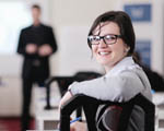 seated woman wearing shirt, jumper and glasses. Out of focus man stands in the background
