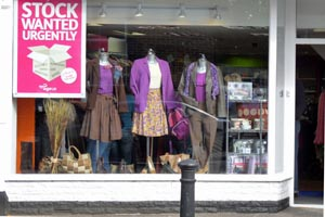 "charity shop window displaying a pink and white poster which reads ""stock wanted urgently"""