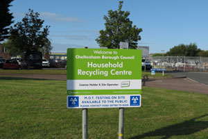 Sign on a grass verge in front of the Swindon Road recycling centre reads 'Household recycling centre' in white letters on a green background