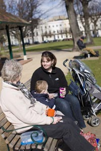 An older woman and a younger woman sit on a park bench on either side of a young child