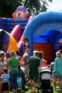 Adults and children in front of a brightly coloured bouncy castle