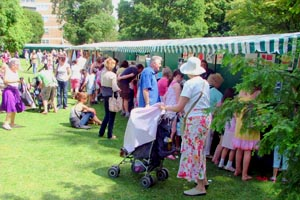Woman in summer hat with pushchair amongst other visitors to the fiesta stalls
