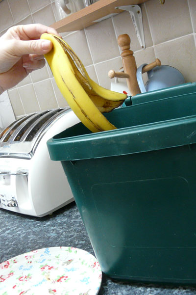 Putting a banana skin into food caddy