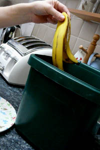 someone putting a banana skin into a green plastic container