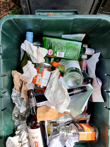 green plastic recycling box full of glass bottles, paper and card