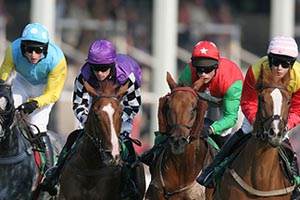 Four jockeys in colourful silks racing astride their horses.