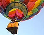 two people in a basket hanging under a colourful hot air balloon