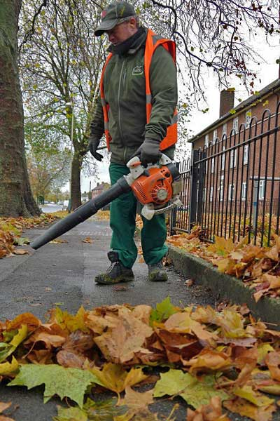 Ubico operative using a leaf blower to clear fallen leaves from a pavement