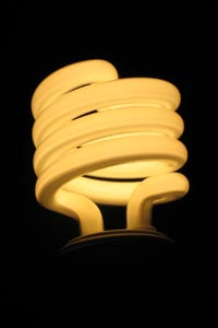 spiral fluorescent light bulb glowing against a dark background