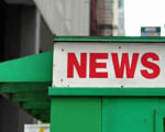 "Red and white sign on the side of a green news stand says ""news"""