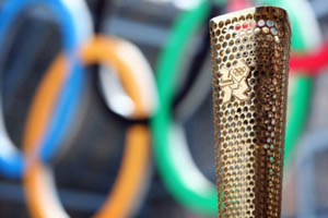 Metallic gold Olympic torch with the Olympic rings in the background (blue, yellow, black, green and red)
