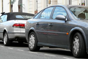 grey hatchback and silver soft-top cars parked in on-street parking bays