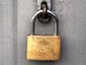 brass coloured padlock against grey metal background