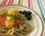 Plate of pasta, olives and vegetables on a colourful striped table cloth