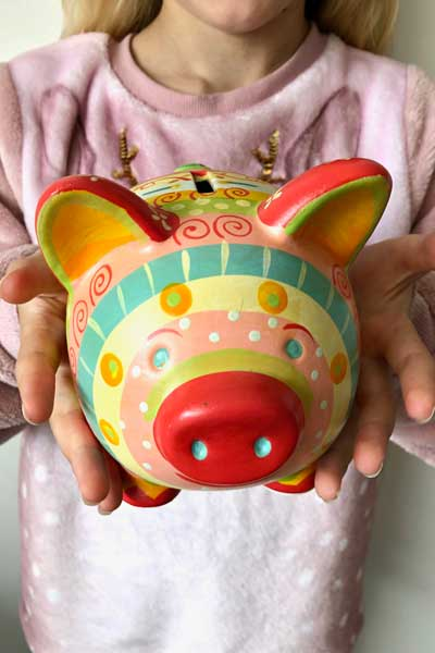 Girl in a pink top holds a colourful patterned piggy bank