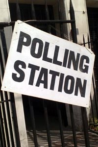 Polling station sign, large black lettering on white background secured to iron railings