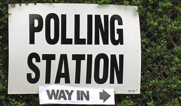 Sign which reads 'polling station - way in' attached to a wire fence with green hedge behind