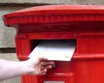 Someone putting a letter into a postbox
