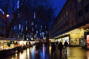 High street scene with Christmas lights reflecting on wet paving slabs