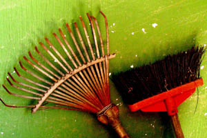 wooden rake and brush with red plastic handle leaning against a green painted wall