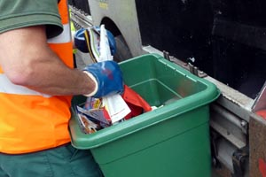A recycling operative emptying a green recycling box