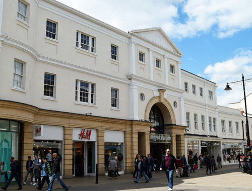 Shop fronts and shopping centre entrance in Regency style with cream and white painted walls and windows