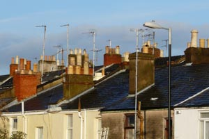 rooftops of terraced houses with many chimneys and aerials