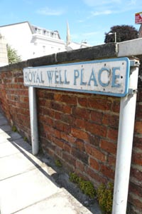 Sign for Royal Well Place - blue lettering on white - against a low brick wall