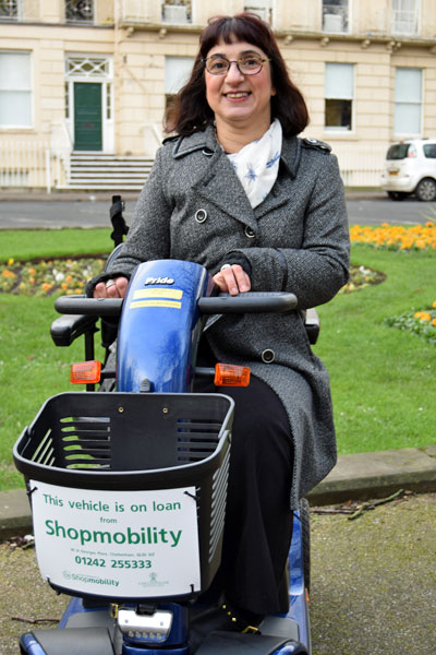 Woman on shopmoblity loan vehicle with the municipal offices in the background