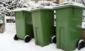 3 green bins out in the snow