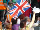 A union flag is held aloft in a crowd of people