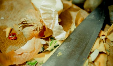 sharp knife and vegetable peelings on a wooden chopping board