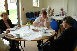 Three people sat around a table at a community event