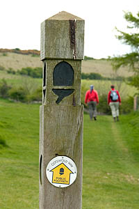 Signpost on the Cotswold Way with walkers in the background