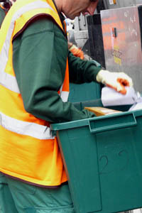 man in high visibility vest sorting through a green recycling box