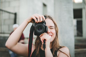 Young woman holding a camera to her face