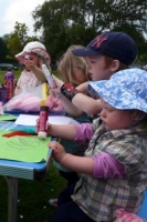 Children sitting around a table in sunhats concentrating intently on their craft activities