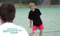 Boy in black t-shirt and pink shorts throwing a tennis ball. Member of staff with his back to the camera. His white t-shirt says sports development team in green letters.