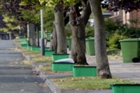 green recycling boxes along a tree lined street